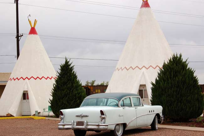 Vintage cars in the parking lot of the Route 66 Wigwam Motel.